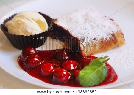 Delicious dessert cherry strudel with berries and ice cream