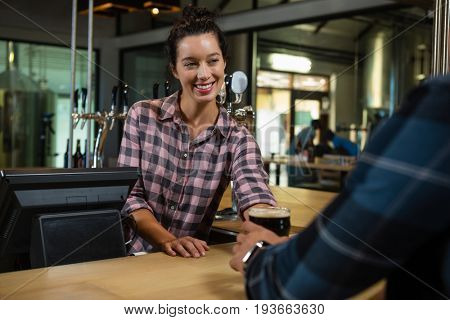 Smiling young barmaid serving drink to male customer at bar counter