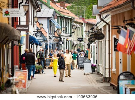 Sigtuna Sweden - 23 July 2013: old town street in City of Sigtuna Sweden Europe. Beautiful sunny day with tourists walking in street.