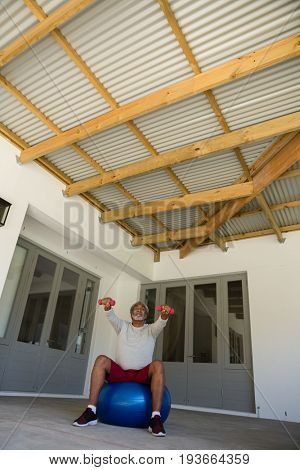 Active senior man exercising with dumbbells on exercise ball in the porch