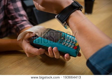 Cropped hand of male customer making payment through contactless payment machinery at bar