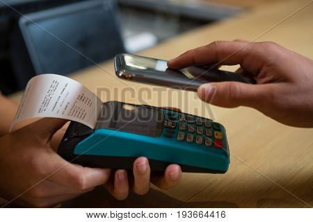 Cropped hand of customer making payment through contactless payment machinery at bar