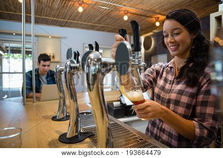 Young smiling barmaid pouring beer from tap in glass at restaurant