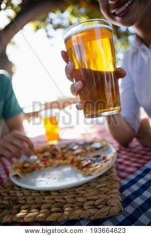 Cropped image of woman holding beer glass at table in outdoor restaurant