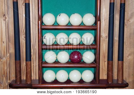 Billiard balls lie on the shelves cue storage and a set of billiards