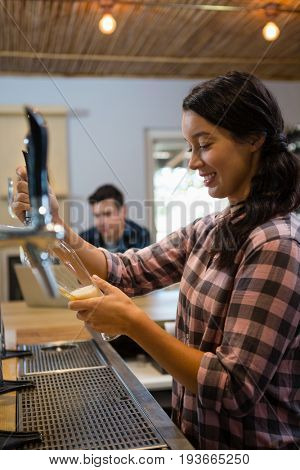 Barmaid pouring beer from tap in glass with customer using laptop in background at restaurant