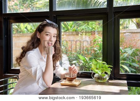 Beautiful happy mixed race girl dress in smart casual mix and stir hot black coffee while look at camera