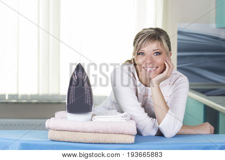 Beautiful young woman is leaning on ironing board looking at camera and smiling while ironing clothes at home.