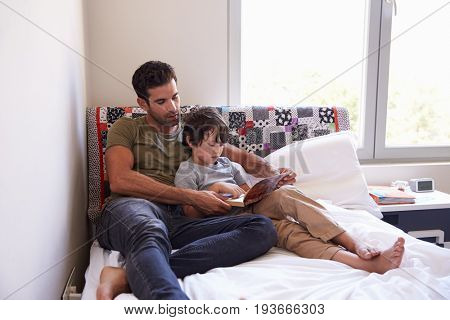 Father And Son Siting On Bed Reading Book Together