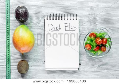 Heathy food for slimming. Notebook for diet plan, fruits and measuring tape on grey wooden table top view mock up.