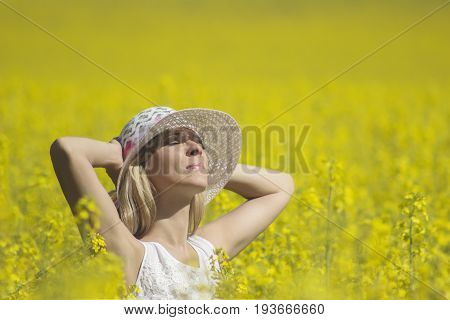 Young woman with a hat enjoying summer on the rape field