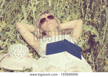 Attractive woman lies in the field and dreams after reading the book