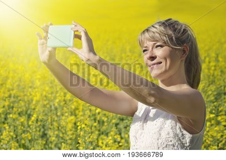 Technology summer holidays vacation and people concept - hands of woman taking selfie by smartphone on rape field