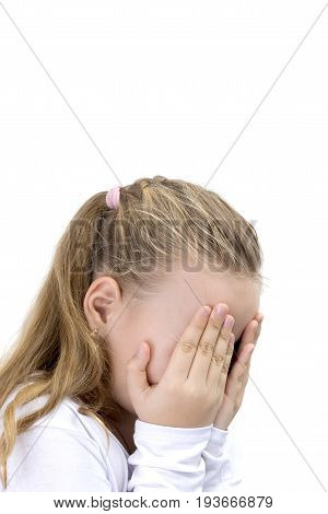 Child covering her face with her hands. Blonde little girl covers her face with her hands isolated. Girl hide face under hands playing hide-and-seek