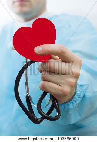 Male medicine doctor wearing hold in hands red toy heart and stethoscope closeup black background. Cardio therapeutist physician make cardiac physical heart rate measure arrhythmia concept