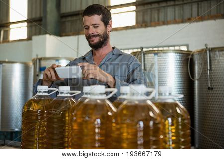 Smiling working taking a photo of olive oil bottles in factory