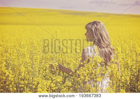 Young woman enjoying nature and sunlight in canola field back view