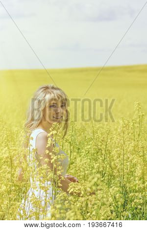 Woman with long hair yellow rapeseed canola field enjoying nature and sunlight