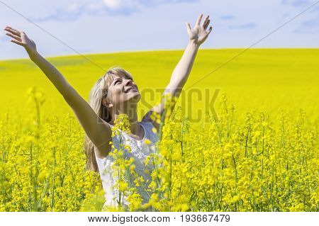 Woman with long hair standing on yellow rapeseed meadow with raised hands. Concept of freedom and happiness
