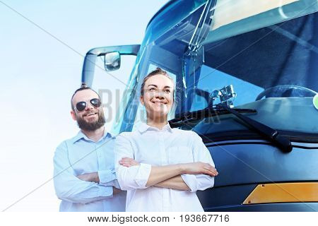 Transportation company, driver and tour operator .  The driver and tour guide are standing in front of the coach