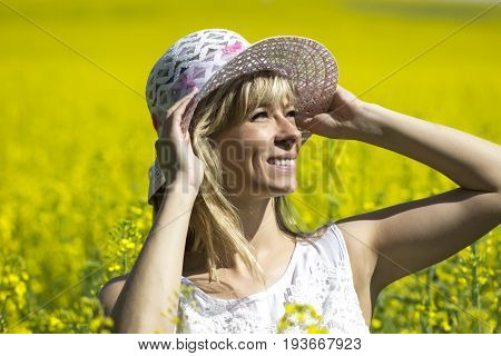 Young woman with a hat enjoying summer on the rape field.