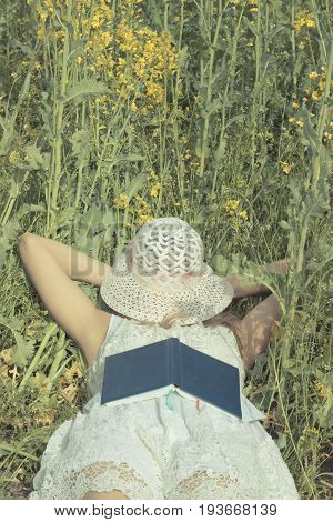 woman sleeping with hat over face her on rape meadow.