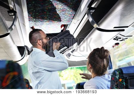Hand luggage. The tourist bus driver inserts a small suitcase into the luggage compartment inside the vehicle.