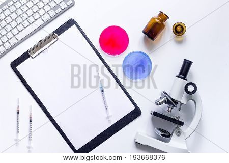 Medical tests. Work table of doctor witn microscope, Petri dish, syringe and ampoule on white background top view..