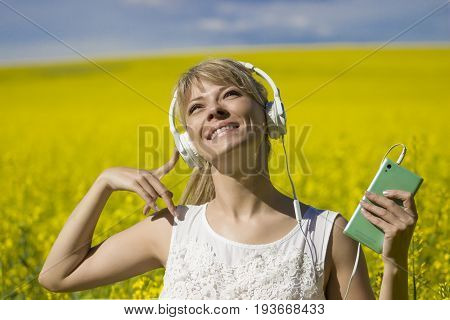 Cheerful young woman listening to music in a canola field.