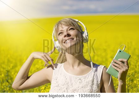 Cheerful young woman listening to music in a canola field