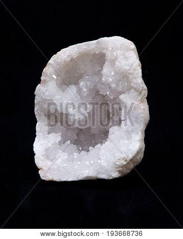Clear crystal quartz geode with crystalline druzy center on black background