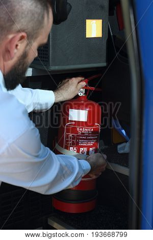 Car fire extinguisher. The bus driver shows the fire extinguisher during the inspection