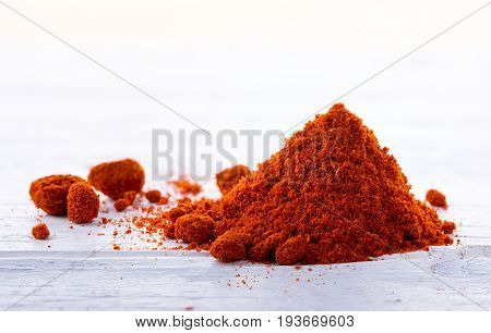 Heap of bell pepper sweat paprika powder on white wooden background.