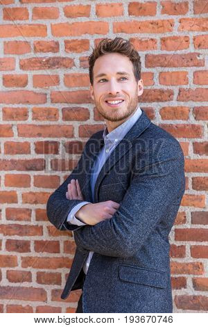 Smart casual businessman on urban city brick wall background lifestyle portrait. Young professional man smiling confident in blazer. Career and entrepreneurship concept.