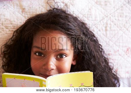 Overhead Portrait Of Girl Lying On Bed And Reading Book