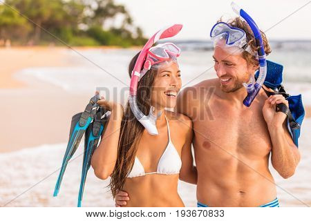 Happy couple laughing together beach fun on summer snorkel travel vacation healthy active lifestyle. Sports leisure young friends doing snorkelling swim activity at Hawaii tropical holidays.
