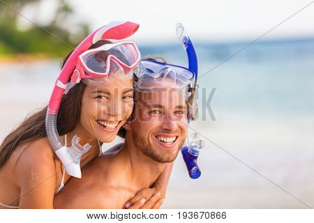 Snorkel beach summer happy couple holiday portrait. Travel vacation snorkelers smiling asian woman, caucasian man living a healthy lifestyle with diving mask at snorkeling tropical vacations.