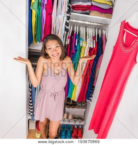 Closet woman can't decide what to wear, confused by outfits needing to organize closet with too many clothing. Funny girl indecision clothes choices, spring cleaning concept. Clothes walk-in closet.