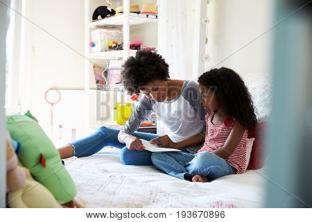 Mother And Daughter Siting On Bed Reading Book Together