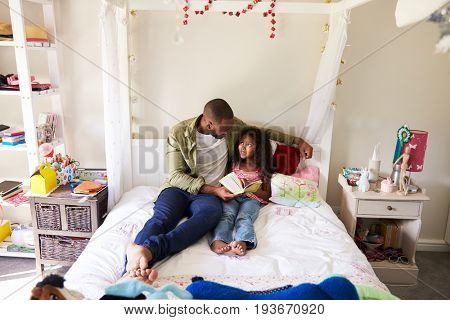 Father And Daughter Siting On Bed Reading Book Together