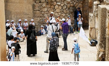 Jerusalem, Israel - May 21, 2017: Israeli Jewish children and people singing and dancing on the street celebrating the Jerusalem day in Israel. The anniversary of reunion Jerusalem, capital of Israel.