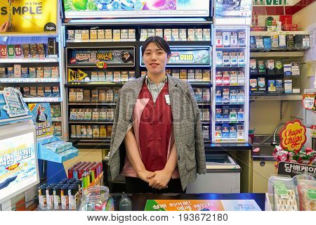 SEOUL, SOUTH KOREA - CIRCA MAY, 2017: indoor portrait of worker at 7-Eleven convenience store. 7-Eleven is an international chain of convenience stores.