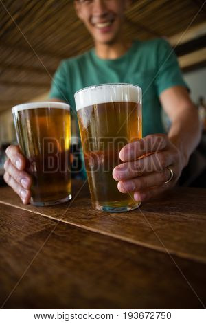 Male bartender serving beer at counter in restaurant
