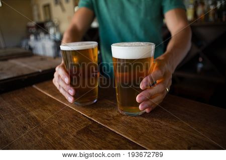 Midsection of bartender serving beer at counter in restaurant