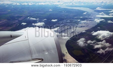 Flying over the clouds. View from plane aircraft passenger window. First seconds after takeoff.
