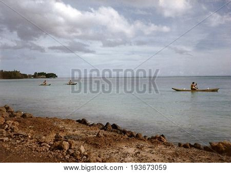 Men paddle outrigger canoes near the shore of the island of Savai'i in Samoa.
