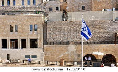 Israel Flag is waving and flying on the wind. The Flag is located near the Western Wall also called Wailing Wall or Kotel. Jerusalem, Israel.