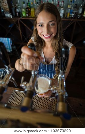 Portrait of beautiful barmaid pouring beer from tap in glass at restaurant