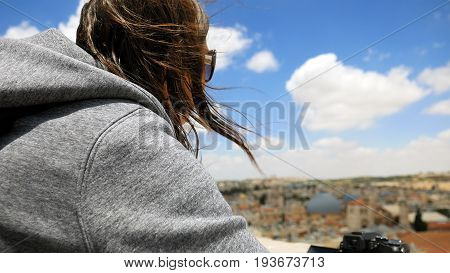 Longhair woman enjoys the Jerusalem cityscape outdoors in windy weather. Her hair is waving and flying in the wind.