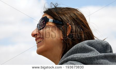Longhair woman in sunglasses smiling and laughing outdoors and enjoys the good summer weather. Her hair is waving and flying in the wind.